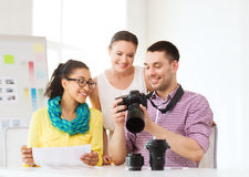 Equipo sonriente con el photocamera que trabaja en oficina Fotografía de archivo