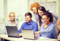 Equipo sonriente con los ordenadores portátiles en oficina fotografía de archivo