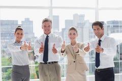 Equipo sonriente de hombres de negocios que dan los pulgares para arriba Imágenes de archivo libres de regalías