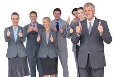Equipo sonriente del negocio que muestra los pulgares para arriba Fotografía de archivo