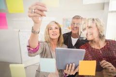 Equipo sonriente del negocio que trabaja en la tableta Imagen de archivo libre de regalías