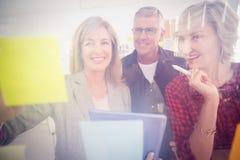 Equipo sonriente del negocio que trabaja en la tableta Imagenes de archivo