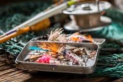 Equipo viejo del pescador con las moscas y las barras de la pesca Imagen de archivo libre de regalías