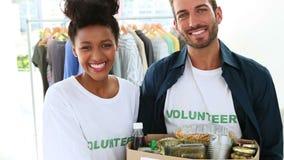 Equipo voluntario feliz que sostiene una caja de la donación de la comida almacen de video