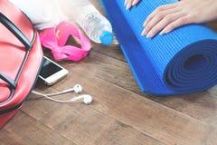 Equipo y accesorios con el teléfono móvil para el entrenamiento de la mujer en el piso de madera Imagen de archivo