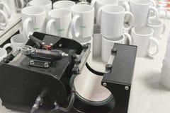 Equipo y tazas de impresión de la sublimación Imagen de archivo