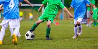 Equipos de fútbol del fútbol de la juventud que golpean el balón de fútbol con el pie en campo de deportes Fotos de archivo libres de regalías