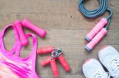 Equipos y accesorios de deporte para la mujer en el fondo de madera con el espacio de la copia Foto de archivo libre de regalías