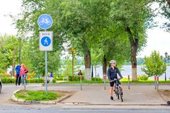An equipped cyclist stands on the sidewalk at a pedestrian crossing royalty free stock photos