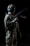 Equipped soldier standing in profile and holding automatic machine raised up. Military man fully dressed in camouflage - a suit, gloves, helmet, goggles stock photography