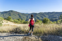 Equipped woman hiking in a high autumn  mountain Royalty Free Stock Images