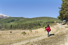 Equipped woman hiking in a high winter mountain. Hiker woman with backpack  in a high winter mountain.Beautiful landscape from Bulgaria Royalty Free Stock Photography