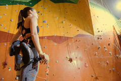 Equipped woman standing behind the climbing wall. Stock Photo