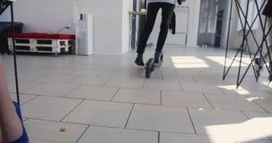 Equitação à moda nova do homem de negócios, pegando fora o 'trotinette' elétrico no escritório na moda moderno Atmosfera moderna  video estoque