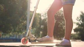 Equitação adolescente da menina em um 'trotinette' em um por do sol Pés e 'trotinette' ao conduzir o close-up video estoque