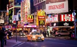 Equitação amarela do carro do táxi através do Times Square Imagem de Stock Royalty Free