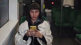 Equitação atrativa da jovem mulher no transporte público usando o smartphone É texting, verificando correios, bate-papos ou video estoque