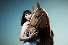 Equitação bonita da mulher em um cavalo marrom Imagens de Stock Royalty Free