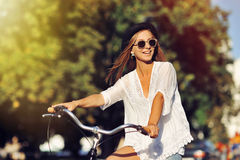 Equitação bonita da mulher na bicicleta Fotografia de Stock
