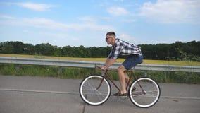 Equitação considerável nova do homem na bicicleta do vintage na estrada secundária Ciclismo desportivo do indivíduo na trilha Equ video estoque