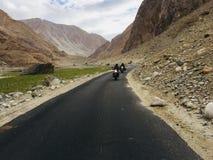 Equitação da bicicleta ao longo das montanhas imagens de stock royalty free