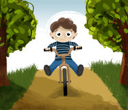 Equitação da criança em uma bicicleta Imagens de Stock