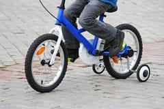 A equitação da criança na bicicleta Imagens de Stock