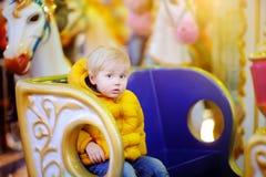 A equitação da criança no carrossel colorido alegre vai círculo Da cidade entretenimento fora para crianças Imagens de Stock