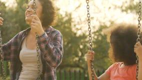 Equitação da mãe e da filha no balanço no parque de diversões, família que tem o divertimento fora vídeos de arquivo