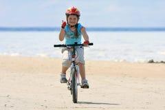 Equitação da menina com a bicicleta ao longo da praia Imagens de Stock