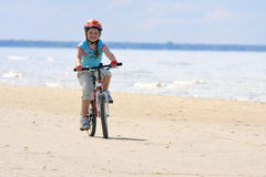 Equitação da menina com a bicicleta ao longo da praia Fotografia de Stock