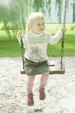 Equitação da menina dos anos de idade no parque em um balanço Imagens de Stock