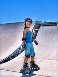 Equitação da menina em patins de rolo no skatepark Fotos de Stock