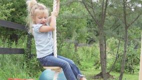 Equitação da menina em um balanço de madeira no verão