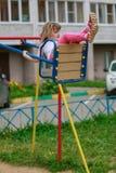 Equitação da menina em um balanço no campo de jogos imagens de stock