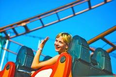 Equitação da menina em uma montanha russa fotografia de stock