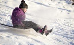 a equitação da menina na neve desliza no tempo de inverno Foto de Stock