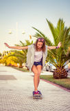 Equitação da moça em um skate fora Imagens de Stock Royalty Free