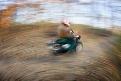 Equitação da motocicleta em um parque da cidade em um outono/dia bonitos da queda (motio Fotografia de Stock Royalty Free