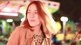 Equitação da mulher no carrossel e acenar à câmera no parque de diversões filme