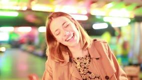 Equitação da mulher no carrossel e acenar à câmera no parque de diversões vídeos de arquivo