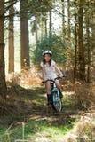 Equitação da rapariga sua bicicleta na floresta Imagens de Stock
