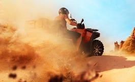 Equitação de Atv na pedreira da areia, nuvens de poeira, bicicleta do quadrilátero fotos de stock royalty free
