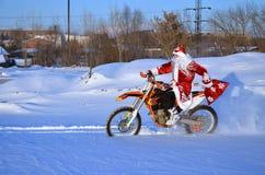 Equitação de Santa Claus em um MX da bicicleta através da neve profunda Imagem de Stock Royalty Free