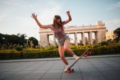 Equitação desportiva nova da mulher no longboard no parque Fotografia de Stock