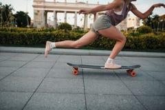 Equitação desportiva nova da mulher no longboard no parque Imagens de Stock