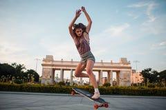 Equitação desportiva nova da mulher no longboard no parque Foto de Stock