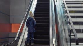 Equitação do adolescente da moça na escada rolante no shopping ou no aeroporto moderno vídeos de arquivo