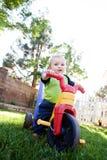 Equitação do bebé em um brinquedo Fotos de Stock