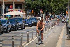 Equitação do ciclista em uma pista da bicicleta em um dia de verão Fotos de Stock